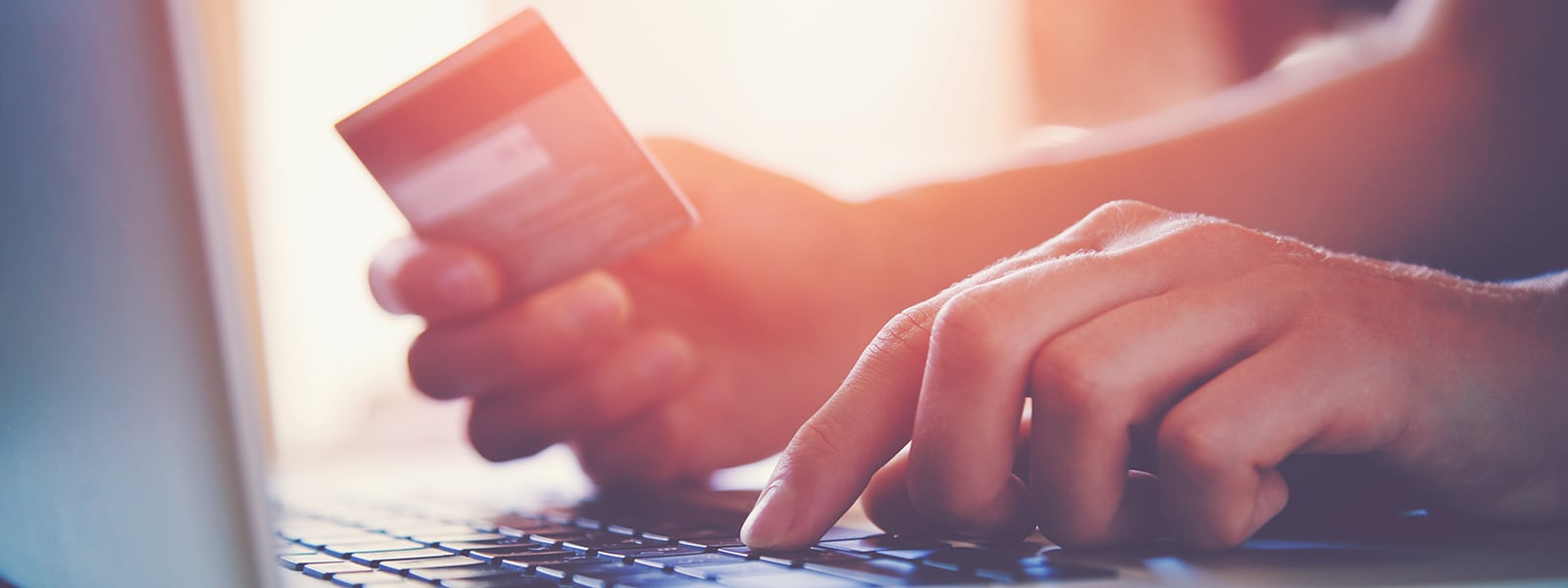 Close-Up of Person Completing an Online Purchase with Credit Card and Laptop | Woodruff